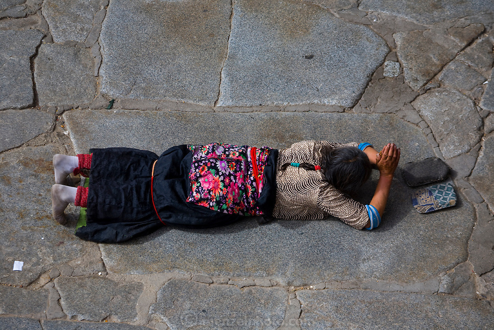 A Buddhist pilgrim prostrates herself and prays in front of the Jokhang Monastery in Lhasa, Tibet. (From the book What I Eat: Around the World in 80 Diets.)
