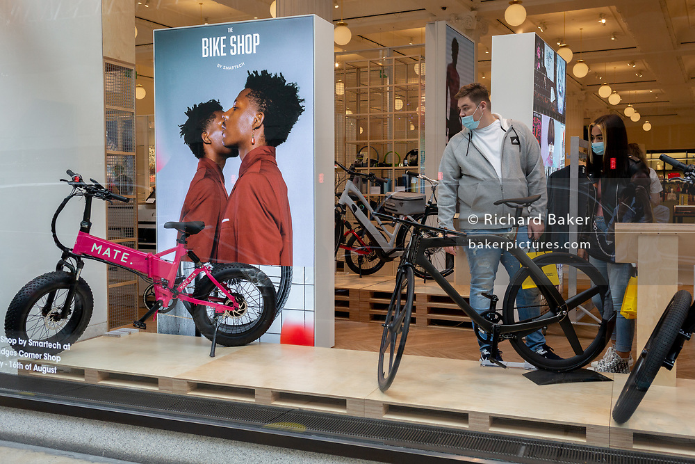 On the day that covid pandemic guidelines for shoppers in England mean that the wearing of face coverings in shops is mandatory, a male shopper wearing a face mask looks at bikes and cycling products in the window of Selfridges on Oxford Street, on 24th July 2020, in London, England.