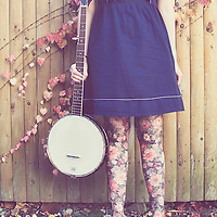 Young female with a banjo in autumn wearing a blue dress with floral tights and autumn leaves