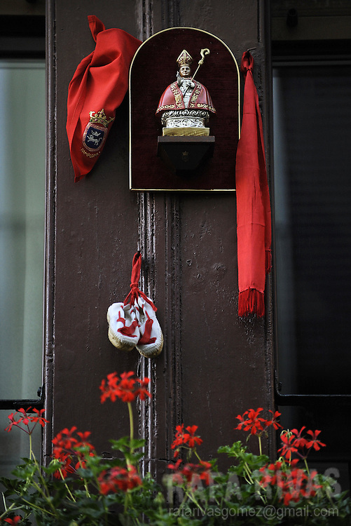 A figure of San Fermin, a red scarf, a belt and a pair of shoes hang from a window in Pamplona, north of Spain, on July 14, 2008, the last day of the San Fermin festivities.