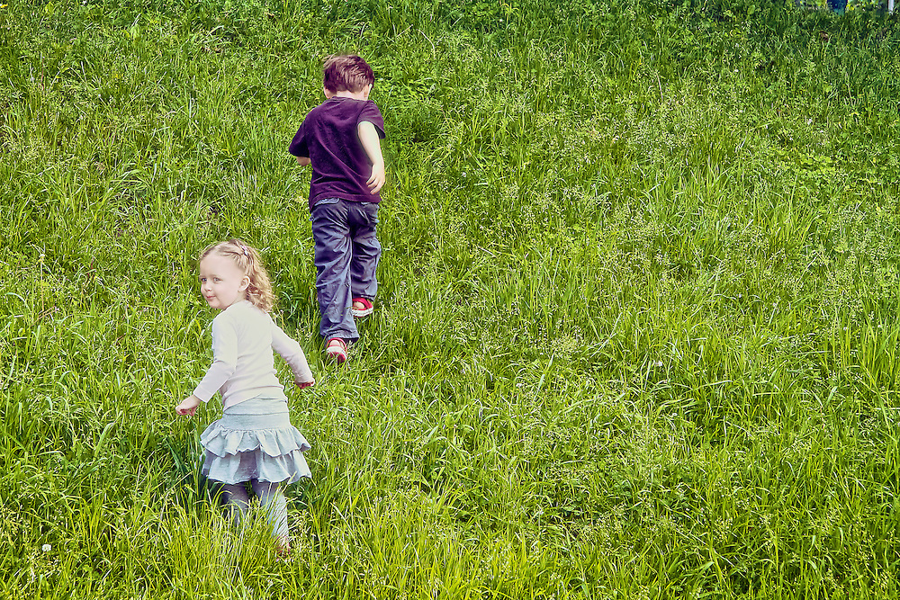 Brother and sister run up a hill in summertime.