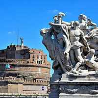 Allegorical Statue on Ponte Vittorio Emanuel II in Rome, Italy <br /> As you walk along the 354 feet of the Ponte Vittorio you will encounter four allegorical sculptures. They were carved from travertine marble in 1911. They symbolize Oppression Conquered, Loyalty to the State, Freedom and the Unification of Italy.  The bridge was designed by Ennio De Rossi and opened on the 50th anniversary of Italy&rsquo;s unification.  In the background is the Mausoleum of Hadrian named Castel Sant&rsquo;Angelo.
