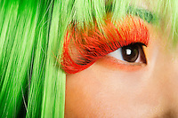 Extreme close-up of young woman's face with false eyelashes and green wig