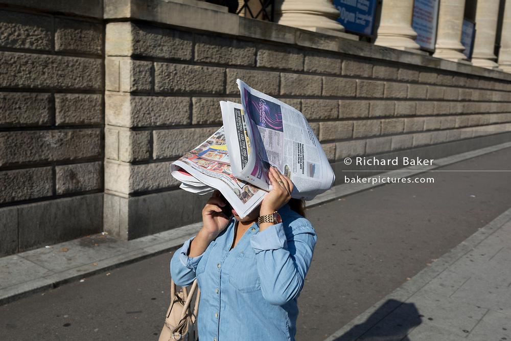 A woman shades her head with a newspaper while walking at Elephant & Castle, on 10th October 2018, in London, England.