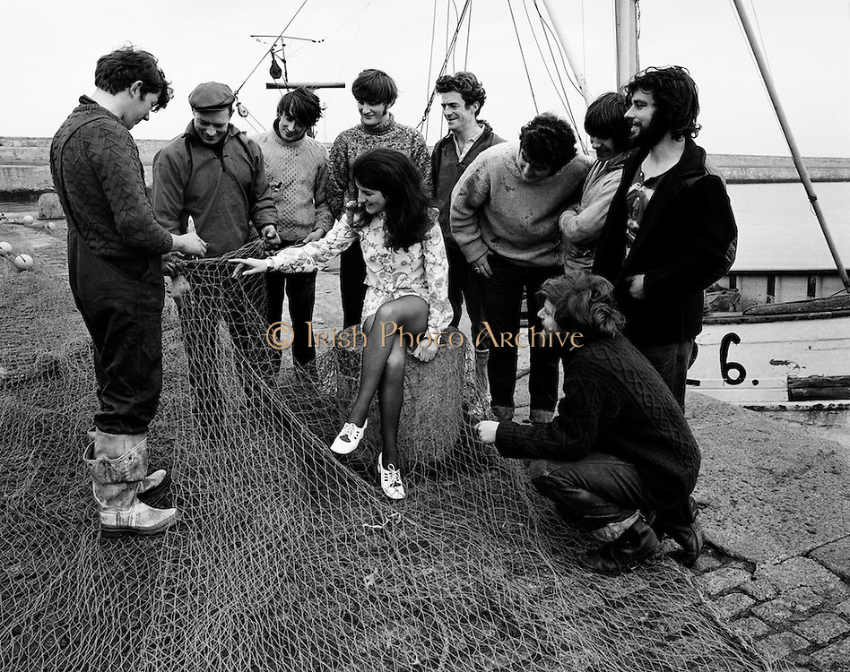 Ann Scallan, 'Miss World Fishing', is surrounded by local fishermen on the harbour wall at Dun Laoghaire. To present the more glamorous side of the fishing industry, Bord Iascaigh Mhara organised a Miss World style competition for young women within the fishing industry. The winner was selected from six finalists from fishing ports around the country.<br /> 13/03/1971