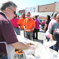 Tupelo Chilifest volunteer Tommy Green, left, serves up another cup full of chili that was provided by Barbaque By Jim for the lunch schdule of events at this year's festival downtown.