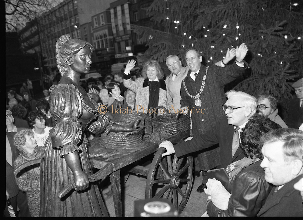 """Molly Malone Statue Unveiled. (R93)..1988..20.12.1988..12.20.1988..20th December 1988..""""Dublin's Fair City"""" received a millenniun gift to commemorate her most famous daughter, Molly Malone, when Jurys Hotel Group plc presented a specially commissioned sculpture to the people of Dublin. The sculpture was formally handed over by Michael McCarthy, MD,Jurys Hotel Group, to the Lord Mayor of Dublin, Councillor Ben Briscoe, TD, in an unveiling ceremony today at the corner of Grafton Street, Suffolk Street and Nassau Street..Molly Malone was created and fashioned in her traditional 17th century dress by Dublin born artist, Jeanne Rynhart, who was selected from a number of entries for the statue design, by the Dublin Millennium Board...In the shadow of the Christmas tree, Lord Mayor Ben Briscoe TD, Mr Michael McCarthy MD, Jurys Hotel Group and the artist Jeanne Rynhart are pictured waving for the cameramen at the official unveiling of """"Molly Malone""""."""