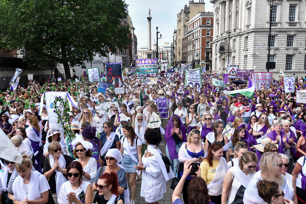 "© Licensed to London News Pictures. 10/06/2018. LONDON, UK.  Over 40,000 women and girls take part in ""Processions"", a mass participation artwork to celebrate one hundred years of votes for women.  Walking together from Park Lane to Westminster participants wear either green, white or purple scarves representing the colours of the Suffragette movement.  Similar walks took place in Belfast, Cardiff and Edinburgh.  Photo credit: Stephen Chung/LNP"