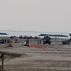 Members of the National Guard stage equipment on the beach at the Grand Isle State Park in Grand Isle, Louisiana, U.S., on Tuesday, May 25, 2010. The BP Plc Deepwater Horizon drilling rig that exploded and collapsed into the Gulf of Mexico continues to release thousands of barrels of oil into the gulf as cleanup and containment efforts continue all along the gulf coast from Louisiana to Florida. Natural wildlife habitats along with marine life are threatened by oil that is now reaching coastal areas throughout Louisiana. Photographer: Derick E. Hingle
