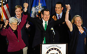 Incumbent Democratic Gov. Dannel P. Malloy, raises his arms over his head with Lt. Gov. Nancy Wyman, left, and wife Cathy Malloy, right, after speaking to supporters at his party's rally, Wednesday, Nov. 5, 2014, in Hartford, Conn. (AP Photo/Jessica Hill)