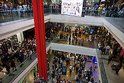 Aerial view of Londoners crowding inside during the opening day of the Westfield Stratford shopping mall. Situated on the fringe of the 2012 Olympic park, Westfield hosted its first day to thousands of shoppers eager to see Europe's largest urban shopping centre. The £1.45bn complex houses more than 300 shops, 70 restaurants, a 14-screen cinema, three hotels, a bowling alley and the UK's largest casino. It will provide the main access to the Olympic park for the 2012 Games and a central 'street' will give 75% of Olympic visitors access to the main stadium so retail space and so far 95% of the centre has been let. It is claimed that up to 8,500 permanent jobs will be created by the retail sector.