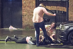 © Licensed to London News Pictures . 01/01/2017 . Manchester , UK . A shirtless man repeatedly kicks another man lying in the gutter as a fight involving several men and women spills over on to St Mary's Parsonage . People on a night out in Manchester City Centre , after midnight on January 1st 2017 . Photo credit : Joel Goodman/LNP