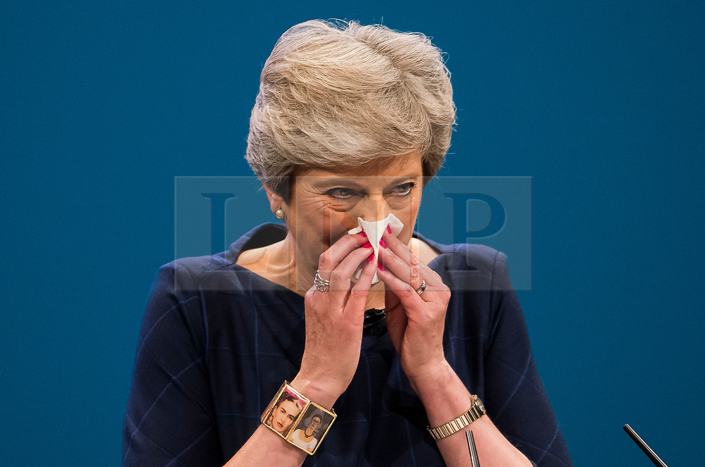 © Licensed to London News Pictures. 04/10/2017. Manchester, UK. British prime minister THERESA MAY wipes her nose while delivering her leaders speech on the final day of the Conservative Party Conference. The four day event is expected to focus heavily on Brexit, with the British prime minister hoping to dampen rumours of a leadership challenge. Photo credit: Ben Cawthra/LNP