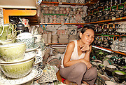 An elderly lady selling ceramic goods in the Ben Thanh Markets, Ho Chi Minh City Vietnam.