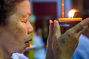 23 OCTOBER 2012 - HAT YAI, SONGKHLA, THAILAND: A woman prays with a candle during a service on the last day of the Vegetarian Festival at Wat Ta Won Vararum, a Chinese Buddhist temple in Hat Yai. The Vegetarian Festival is celebrated in Thai-Chinese communities throughout Thailand. It is the Thai Buddhist version of the The Nine Emperor Gods Festival, a nine-day Taoist celebration celebrated in the 9th lunar month of the Chinese calendar. For nine days, those who are participating in the festival dress all in white and abstain from eating meat, poultry, seafood, and dairy products. Vendors and proprietors of restaurants indicate that vegetarian food is for sale at their establishments by putting a yellow flag out with Thai characters for meatless written on it in red.  PHOTO BY JACK KURTZ