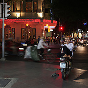 A man rests on his motor bike at night time on a street corner in Ho Chi Minh City, Vietnam. 3rd March 2012. Photo Tim Clayton
