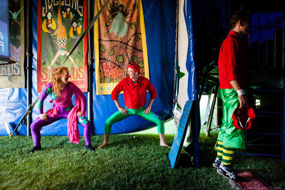 Sarah Tiffin, 17, of Oakland, Calif., and Doug Stewart, 18, of Walpole, Mass., crack each other up while warming up with Keenan Wright-Sanson,  right, 17, of Saratoga Springs, N.Y., just outside the big top during the Circus Smirkus show at Fullington Farm Field in Hanover, N.H., on July 5, 2014. The youth circus performed on Saturday and Sunday. (Valley News - Will Parson)