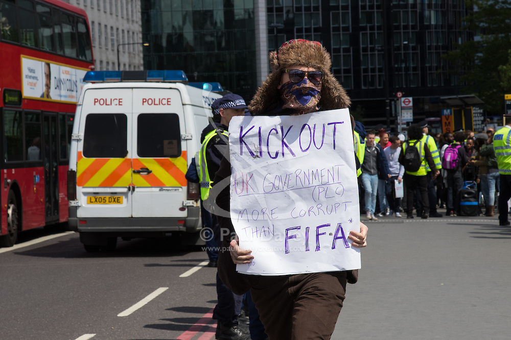 ter, London, May 30th 2015. Anti-austerity campaigners bring traffic on Westminster Bridge as they paint and hang a banner off the bridge highlighting an alleged £120 billion owed in taxes as compared to the proposed £12 billion cuts to welfare. PICTURED: Aprotester 's banner claims Cameron's UK government is more corrupt than FIFA