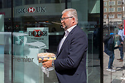 Passing a branch of a HSBC bank, businessman on his lunch-break carries his takeaway back to his office with a wooden spoon in his mouth on Moorgate in the City of London, the capital's financial district - aka the Square Mile, on 8th August, in London, England.