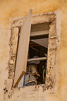 Looking up through a window in Arles, France to  a collection of traditionally dressed dolls.