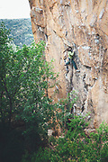 High angle view of Climber reaching across for handhold on rock face