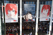 The IFA (Internationale Funkausstellung) in Berlin is the World's biggest trade fair for consumer electronics..Miss IFA, the red haired beauty, is the ever present face of the fair. Visitors are waiting for the fair to open its gates, in the morning.