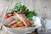 Plate with spaghetti dressed with red mullet sauce, decorated with parsley and cherry tomatoes.
