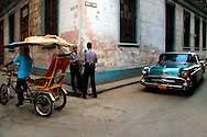 Old American car, police, and bicitaxi at a corner in Havana, Cuba.