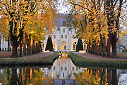 Royaumont Abbey seen through trees, reflected in lake, Val-d'Oise, France. The Cistercian Abbey was founded 1228 by St Louis, and dissolved 1789 after the French Revolution. Photograph by Manuel Cohen.