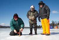 """With limited ice conditions at their usual spot over by Governor's Island Mark Gere, Peter Linero and Paul Gere try their luck on Lake Waukewan where  wind was giving them a few """"false alarms"""" on their tip ups as they began fishing for the Great Meredith Rotary Ice Fishing Derby.  (Karen Bobotas/for the Laconia Daily Sun)"""