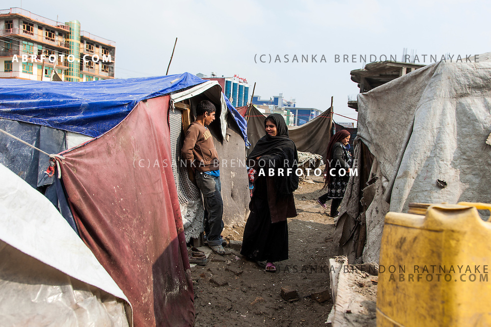 Refugees talking in a small alley amoungst ten houses in a refugee camp