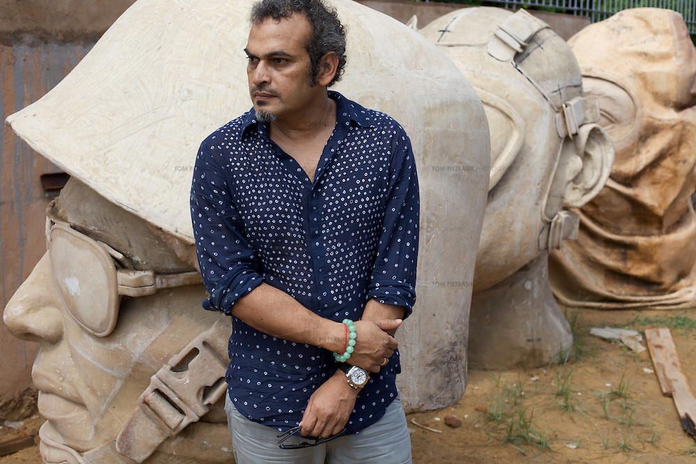 "Subodh Gupta, contemporary artist with one of his sculptures outside his recently completed studio in Gurgaon, a satellite town of Delhi...Gupta's most celebrated sculptures are constructed from common domestic items including the steel pots and pans that are a feature every Indian home. Of the kitchen-ware that forms the basis of his work, Gupta says,..""The poor, the middle class and the rich use it at home. In this country, how many people have the utensils but they starve because there is no food?""..Gupta was brought up, one of six children, to a railway-worker father in a north Indian village. ..Gupta's work fetches such huge sums of money. Two versions of his Mind Shut Down, modeled on the human skull and constructed entirely of steel kitchen utensils recently sold for EUR1 million each...Photo: Tom Pietrasik.Gurgaon, Haryana. India. .July 23rd 2009"