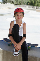 Teenage boy (13-15) with skateboard at skateboard park portrait