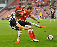 Picture by Richard Land/Focus Images Ltd +44 7713 507003<br /> 27/08/2013<br /> James O'Brien of Barnsley and Jay Rodriguez of Southampton wrestle for the ball during the Capital One Cup match at Oakwell, Barnsley.