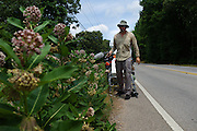 """DACULA, GA – JUNE 6, 2014: Karl Bushby stops to film a row of flowers along Highway 124, east of Atlanta, Georgia. Bushy walks about 20 miles a day, and has admitted that his quest to get permission to travel through Russia is a long shot. """"If I skip Russia and just start walking through China, I've failed.""""<br /> <br /> Karl Bushby is trying to complete the longest walk in history. Unless the Russians stop him. As a 45 year-old Brit, Bushby been traveling around the world on foot since 1998. In the most recent leg of his journey, Bushby is walking to Washington, D.C. to petition the Russian Embassy to lift a visa ban that prohibited him from continuing his hike through Russia."""