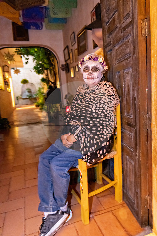 An elderly Mexican woman wearing skeleton face paint sits in her doorway during the Dead of the Dead festival in San Miguel de Allende, Mexico. The multi-day festival is to remember friends and family members who have died using calaveras, aztec marigolds, alfeniques, papel picado and the favorite foods and beverages of the departed.