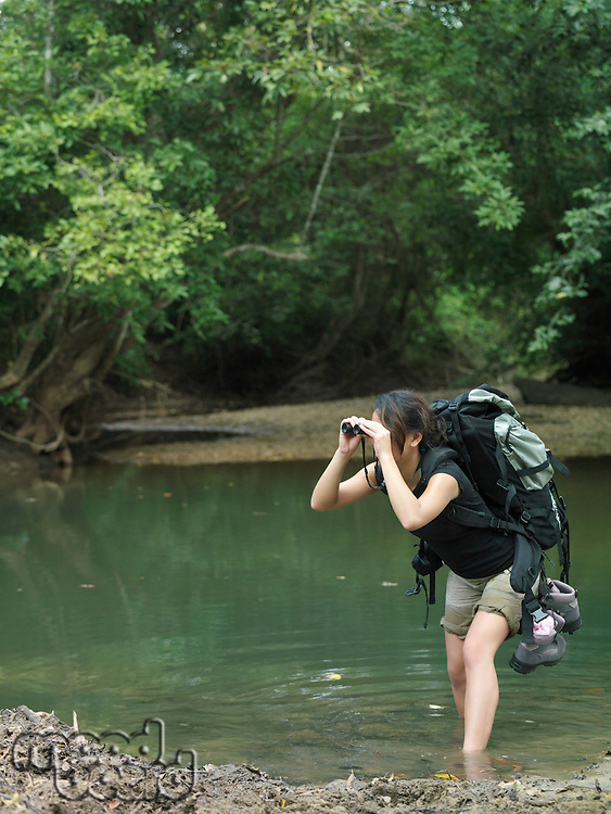 Young woman standing in water carrying backpack looking through binoculars