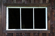 A window frame in the Larson milk shed at Burgoyne Bay. The Larson milk shed was built in the 1940's and used through the early 1960's.  Photographed in Burgoyne Bay Provincial Park on Salt Spring Island, British Columbia, Canada.