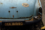 "Detail of a rusty Wartburg 312 car standing at the kerbside in an eastern Berlin district. A sticker with the letters DDR as the German Democratic Republic (DDR in German and GDR in English) as East Germany was called during the Cold War. Any car was a highly-prized possession when ownership of luxury goods like vehicles aroused suspicion for other than Communist Party officials. This car may have been someone of rank or influence. The GDR was a self-declared socialist state, referred to in the West as a ""communist state"" in the Soviet Sector of occupied Germany created after the second world war and partitioned when DDR leaders built the Berlin Wall that eventually segregated Germany and Europe. The East Germany state existed from 7 October 1949 until 3 October 1990 and was a potent symbol of a divided Europe during the Cold War..."