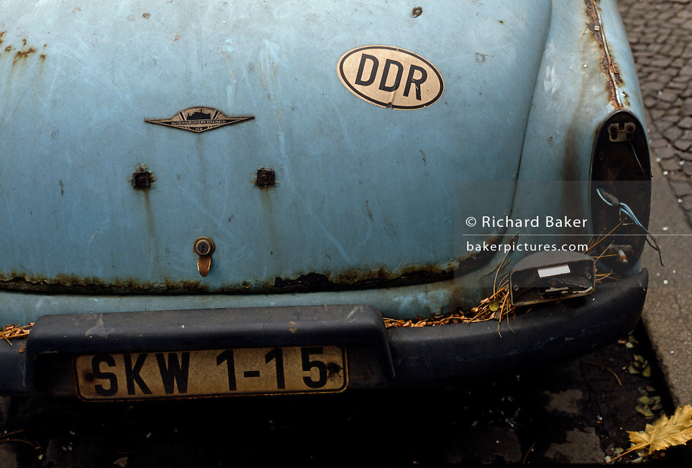 """Detail of a rusty Wartburg 312 car standing at the kerbside in an eastern Berlin district. A sticker with the letters DDR as the German Democratic Republic (DDR in German and GDR in English) as East Germany was called during the Cold War. Any car was a highly-prized possession when ownership of luxury goods like vehicles aroused suspicion for other than Communist Party officials. This car may have been someone of rank or influence. The GDR was a self-declared socialist state, referred to in the West as a """"communist state"""" in the Soviet Sector of occupied Germany created after the second world war and partitioned when DDR leaders built the Berlin Wall that eventually segregated Germany and Europe. The East Germany state existed from 7 October 1949 until 3 October 1990 and was a potent symbol of a divided Europe during the Cold War..."""