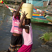 Kenya. Mbita on shore of Lake Victoria. Homa Bay county. Two very young girls collecting water from the lake. One puts a heavy can on her head.