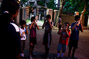 Razia Shabnam (in dark blue) conducts a training session in Biyam Samiti park with children from the area of Kidderpore, Calcutta, West Bengal, India. Razia Shabnam, 28, was one of the first women boxers in Kolkata. She was also the first woman in her community to go to college. She is now a coach and one of only three international female boxing referees in India.  Photo by Suzanne Lee for Panos London