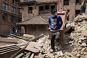 Devastating April 2015 Nepal Earthquake. People salvaging furniture from their collapsed home in Bhaktapur, one of three ancient royal cities of Kathmandu Valley and a UNESCO World Heritage Site. The town was severely damaged, with many old buildings destroyed.