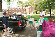 Ohio University's President Roderick McDavis (Right) assists first year student and First Lady Deborah McDavis help a first year student move into their residence hall.  Photo by Ben Siegel