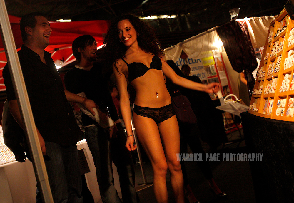 """LYON, FRANCE - DECEMBER 13: An erotic dancer talks with a customer at a stall at the """"Les Salon de l'Erotisme"""", December 13, 2008, in Lyon, France. The erotic exhibition has been running annually since 2001, and is currently travelling throughout France from November 2008 and finishes in April 2009. The exhibition attracts singles and couples of all ages and consists of live sex shows, erotic dancers and stalls selling sex toys, erotic clothing and adult products. (Photo by Warrick Page)"""