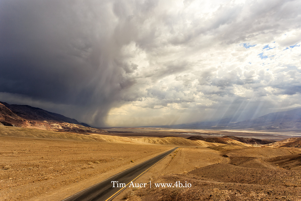 Death Valley, California, USA<br /> A road bisects the clouds that are carrying a relatively uncommon weather phenomenon in Death Valley: rain. <br /> <br /> As expected for Death Valley in July, it was hot, but nothing unusual at about 121F/50C. What was more unusual was the storm that blew in later that day. The storm front came in over the Black Mountains in the southeast and moved northwest up the valley. There were raindrops on the valley floor, lightning high in the mountains, and fierce wind everywhere blowing sand. This photo was taken as the storm crested over the range.  The resulting change in air pressure mixed with extremely hot air lead to violent turbulence and sandstorms, and flash floods in all the washes. <br /> <br /> Death Valley is a world of extremes. As one of the hottest and driest places on the planet, it supports a staggering amount of wildlife, and despite the lack of water, some of its most prominent landscapes are the result of water erosion.  Captured in this photo is evidence of a land shaped by several of the earth&rsquo;s most transformational forces: water erosion, wind erosion, volcanic, and plate tectonics like basin/range extension and earthquake. <br /> <br /> Canon EOS 6D; Canon EF 17-40mm f/4L USM; handheld<br /> 1/500s; f/9; 102mm; ISO 100<br /> Post Processing done using Lightroom 5.7.1