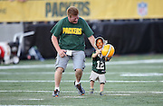 A father chases his young son who is wearing team apparel as he runs onto the field before the Green Bay Packers 2016 NFL Pro Football Hall of Fame preseason football game against the Indianapolis Colts on Sunday, Aug. 7, 2016 in Canton, Ohio. The game was canceled for player safety reasons due to the condition of the paint on the turf field. (©Paul Anthony Spinelli)