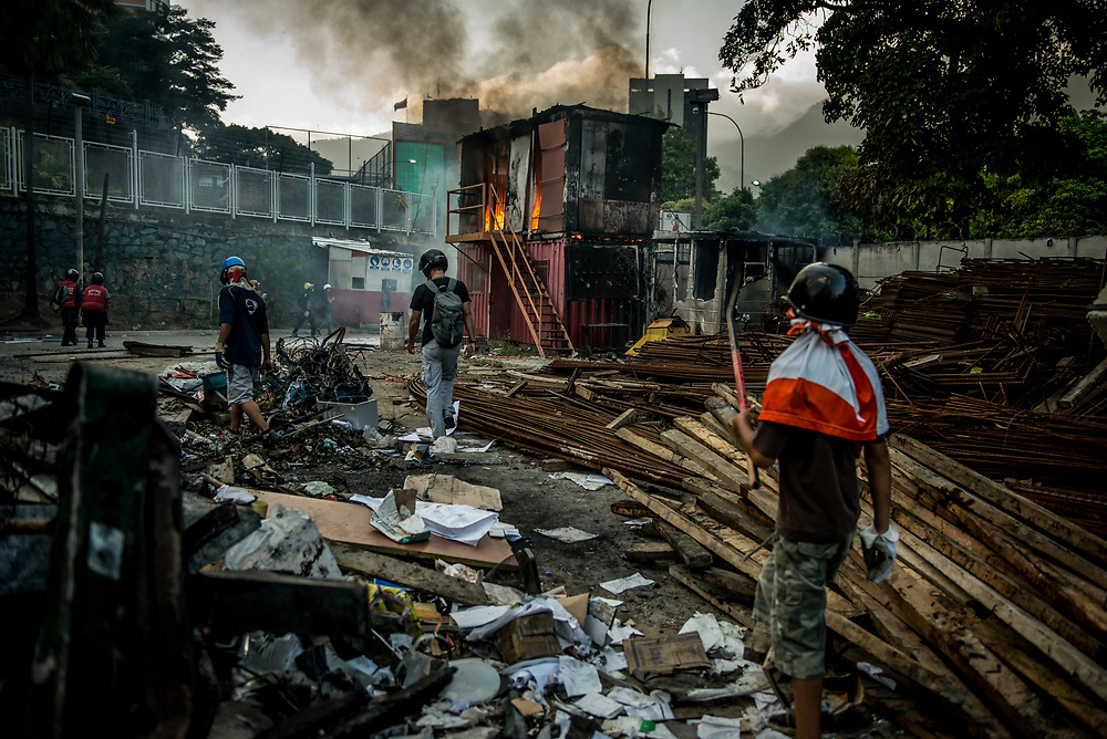 CARACAS, VENEZUELA - MAY 24, 2017:  Anti-government protesters broke into and looted materials from an Odebrecht construction supply hub to build a road block, then burned the office down.  Millions of dollars have been stolen from state coffers  through corrupt politicians' shady dealings with Odebrecht.   The streets of Caracas and other cities across Venezuela have been filled with tens of thousands of demonstrators for nearly 100 days of massive protests, held since April 1st. Protesters are enraged at the government for becoming an increasingly repressive, authoritarian regime that has delayed elections, used armed government loyalist to threaten dissidents, called for the Constitution to be re-written to favor them, jailed and tortured protesters and members of the political opposition, and whose corruption and failed economic policy has caused the current economic crisis that has led to widespread food and medicine shortages across the country.  Independent local media report nearly 100 people have been killed during protests and protest-related riots and looting.  The government currently only officially reports 75 deaths.  Over 2,000 people have been injured, and over 3,000 protesters have been detained by authorities.  PHOTO: Meridith Kohut