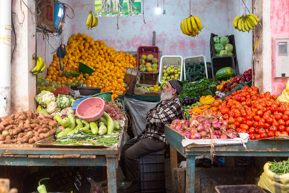 ESSAOUIRA, MOROCCO - May 11th 2018 - Grocer watches TV at a fruit and veg stand in Essaouira, Morocco