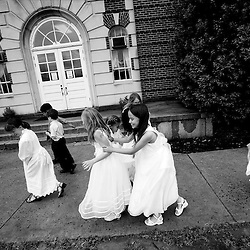 Wearing their white First Communion dresses, second grade students from the Roanoke Catholic School, Madison Monsour (middle left), and Andrea Secamiglio (middle right), run from the wind and rain after the May Crowning ceremony at St. Andrew's Catholic Church in Roanoke, Virginia. May is the Month of Mary, the mother of Jesus, and Catholics have long honored her by placing a crown on her image in a May Crowning Ceremony.